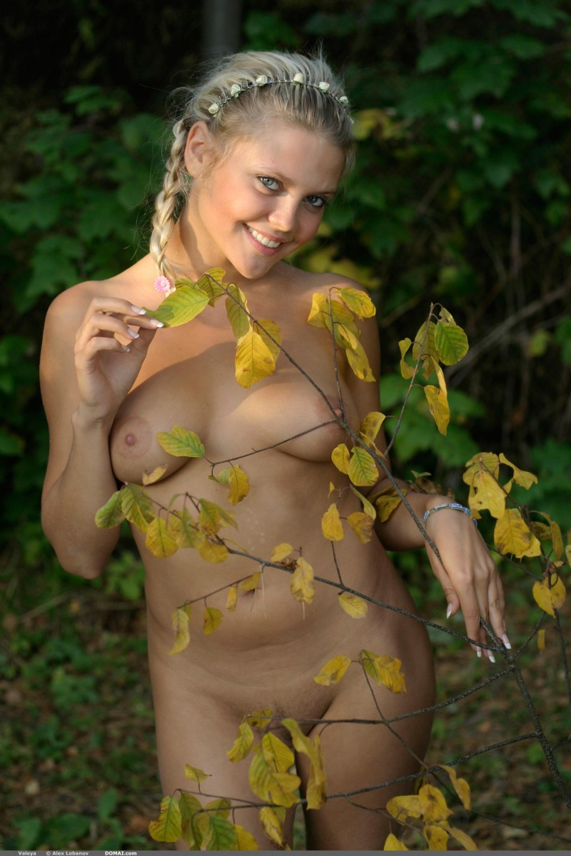 Голая блонда на поляне среди цветов