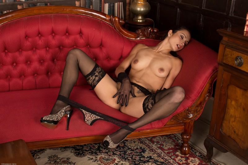 Возбужденная красоточка на красном диване